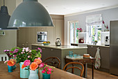 View past flower arrangements on wooden table into kitchen with island counter