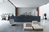Designer furniture in front of kitchen counter in industrial loft apartment