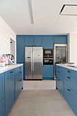 Fitted kitchen with azure-blue cabinets and island counter