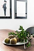 Obstteller und Blätterzweig auf Esstisch mit Mahagoni-Platte