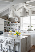 Pendant lamps above island counter with bar stools in white, country-house kitchen