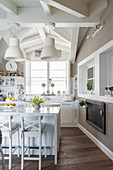 Pendant lamps above island counter with bar stools in country-house kitchen