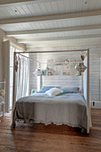 Double, four-poster bed in bedroom with white-painted wooden walls