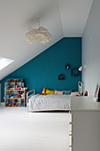 Child's attic bedroom with petrol-blue accent wall