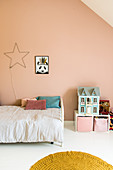 Child's attic bedroom with pink wall