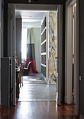 View of marble pillar and bookcase seen through open door