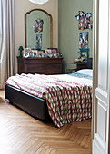 Double bed and antique chest of drawers with mirror in bedroom