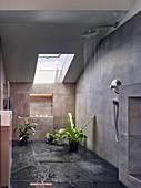 Running water in open shower area of grey bathroom