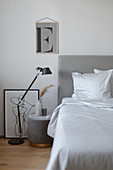 Bedside table and black lamp on floor next to bed with grey headboard and white bed linen