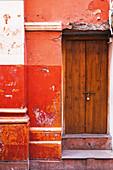 Rote Hauswand mit Holztüre und abgeblätterter Farbe
