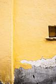 Gelbe Hauswand mit Nischenöffnung und abgeblätterter Farbe