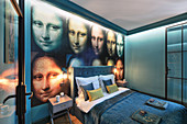 Petrol-blue bedroom with Mona Lisa wallpaper on wall behind bed