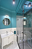 Elegant bathroom with petrol-blue walls and stucco ceiling elements