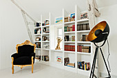 Gilt carved Louis XV armchair in white room with built-in shelving and theatrical light