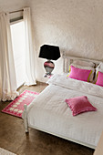 Pink cushions on white bed in bedroom with pink carpet