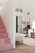 Pink staircase in open plan bedroom with freestanding bath