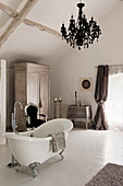 Freestanding bath in room with french drawers, silver carved French chair and black chandelier