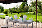 Garden lights on wooden table with design chairs under parasol in garden