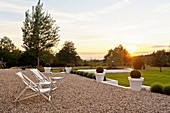 Pair of deck chairs on gravel terrace with garden views at sunset