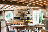 Rustic kitchen with French wooden dining table, ceilings beams, glass chandelier and traditional Camargue-style dining chairs
