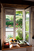 Fresh vegetables arranged in baskets on the sill of an open window set into a thick stone wall
