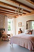 Antique, Persian, embroidered quilt on bed in bedroom with stone walls and wooden ceiling beams