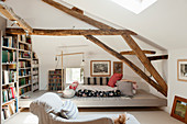 Attic room with wooden ceiling beams, large book case, floor cushions and chaise longue