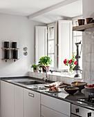 Antique ornamentd on windowsill in fresh modern kitchen in 18th century Luberon farmhouse.