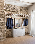 Clothes rails, chest of drawers and mirror in bedroom with stone wall