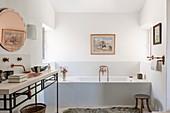 Washstand with brass sink and bathtub in bathroom