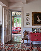 Red-painted cabinet and carved chair under portrait in hallway with decorative tiled floor