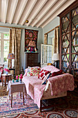 Pink throw on sofa in front of tall, antique bookcase with glass doors