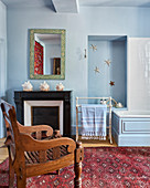Carved wooden chair in light blue bathroom with seashells