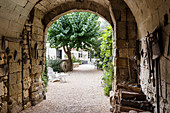 Arched, stone entrance with old farm tools hung on walls