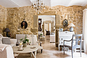 French travertine floors, bureau, stone walls and seating area in living room