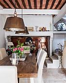 Große Metallpendelleuchten über Esstisch aus Holz, im Hintergrund Treppe