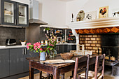 Old fireplace and 19th century table in modern kitchen