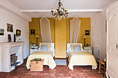 Twin bedroom with yellow accent wall and original, 18th-century terracotta floor tiles