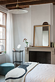 Double bed, fireplace and mirror on mantelpiece in bedroom