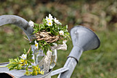 A small bouquet of wood anemones and primrose flowers with a grass cuff and lace ribbon,