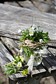 A small bouquet of wood anemones with a grass cuff and lace ribbon