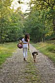 Woman walking with dog in woods