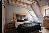 Luxurious double bed in bedroom with wooden ceiling and skylight