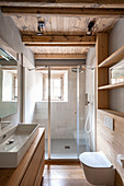 First floor bathroom features wooden walls and large designers sink