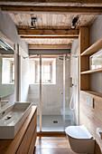 Badezimmer mit Holzmöbeln, Designer-Waschbecken und Duschbereich