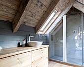Waschtisch aus Holz und Duschbereich im Badezimmer im Dachgeschoss