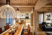 Windlichter auf Esstisch aus Holz in offenem Wohnraum mit Holzdecke