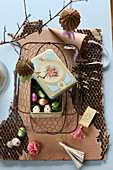 Vintage-style Easter arrangement with tin in wire basket on cardboard