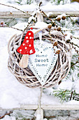 Wreath decorated with wooden fly agaric mushroom, heart and larch cones in snow
