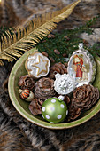Vintage-style Christmas tree decorations and pine cones in bowl